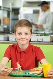 Allievo maschio che si siede alla Tabella nel cibo del self-service di scuola non sano Fotografia Stock
