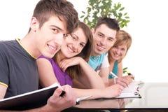 Allievo maschio che studia con i suoi compagni di classe Fotografie Stock