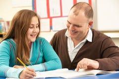 Allievo maschio che studia nell'aula con l'insegnante Immagine Stock Libera da Diritti