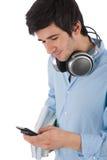 Allievo maschio che trasmette i libri della holding del messaggio di testo Fotografie Stock