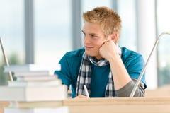 Allievo maschio con i libri che si siedono alla tabella Fotografie Stock Libere da Diritti