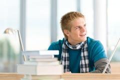Allievo maschio con i libri che si siedono alla tabella Fotografia Stock