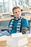 Allievo maschio con il libro che si siede nell'aula Immagini Stock
