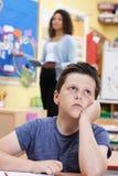Allievo maschio della scuola elementare che fantastica nella classe Fotografie Stock Libere da Diritti