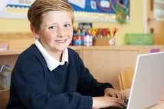 Allievo maschio della scuola elementare che utilizza computer portatile nella classe del computer Fotografia Stock Libera da Diritti