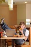 Allievo maschio in pizzeria con il computer portatile Immagini Stock