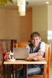 Allievo maschio in pizzeria con il computer portatile Immagine Stock