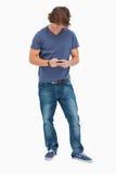 Allievo maschio sorridente che per mezzo del suo cellulare Fotografia Stock