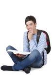 Allievo maschio sorridente che si siede sul pavimento con il libro Fotografia Stock