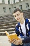Allievo maschio sulla città universitaria con i manuali Immagini Stock