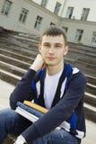 Allievo maschio sulla città universitaria con i manuali Fotografia Stock Libera da Diritti