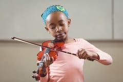 Allievo messo a fuoco che gioca violino in un'aula Immagini Stock Libere da Diritti