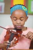 Allievo messo a fuoco che gioca violino in un'aula Fotografie Stock Libere da Diritti