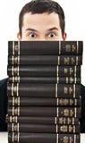 Allievo nascosto dietro un mucchio dei libri Immagine Stock