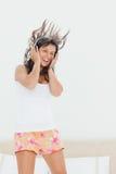 Allievo in pigiama che elenca alla musica mentre saltando Fotografie Stock
