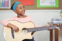 Allievo sorridente che gioca chitarra in un'aula Fotografia Stock