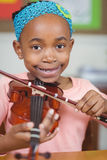 Allievo sorridente che gioca violino in un'aula Immagini Stock