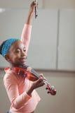 Allievo sorridente che gioca violino in un'aula Fotografia Stock Libera da Diritti