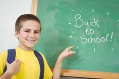 Allievo sorridente che indica sopra di nuovo al segno della scuola sulla lavagna Immagine Stock