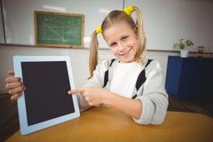 Allievo sorridente che indica sulla compressa in un'aula Immagine Stock