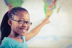 Allievo sorridente che indica sulla mappa di mondo in un'aula Fotografie Stock Libere da Diritti