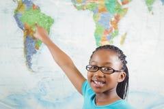 Allievo sorridente che indica sulla mappa di mondo in un'aula Fotografia Stock Libera da Diritti
