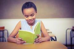 Allievo sorridente che legge un libro Immagini Stock