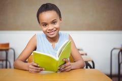 Allievo sorridente che legge un libro Immagine Stock