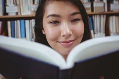 Allievo sorridente che legge un libro Fotografie Stock Libere da Diritti