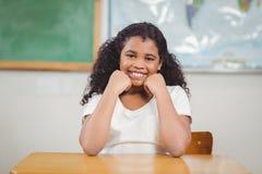 Allievo sorridente che si siede in un'aula Fotografie Stock Libere da Diritti
