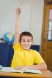 Allievo sorridente che solleva mano in un'aula Fotografia Stock Libera da Diritti