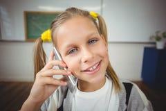Allievo sorridente che telefona con lo smartphone in un'aula Fotografia Stock Libera da Diritti