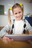 Allievo sorridente che utilizza compressa al suo scrittorio in un'aula Fotografia Stock