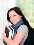 Allievo sorridente con i libri della holding dello zaino Fotografie Stock