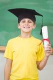 Allievo sorridente con il bordo ed il diploma del mortaio Immagine Stock Libera da Diritti