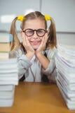 Allievo sorridente fra la pila di libri sul suo scrittorio Fotografia Stock Libera da Diritti