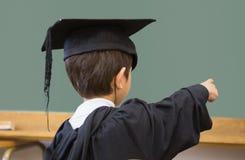 Allievo sveglio in abito di graduazione che indica nell'aula Immagine Stock