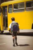 Allievo sveglio che cammina allo scuolabus Fotografia Stock