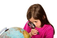 Allievo sveglio che esamina globo tramite la lente d'ingrandimento Fotografie Stock Libere da Diritti