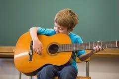 Allievo sveglio che gioca chitarra in aula Immagini Stock Libere da Diritti