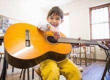 Allievo sveglio che gioca chitarra in aula Fotografia Stock