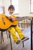 Allievo sveglio che gioca chitarra in aula Immagine Stock
