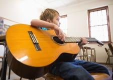 Allievo sveglio che gioca chitarra in aula Immagini Stock