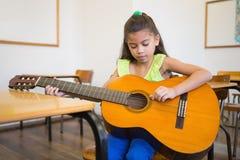 Allievo sveglio che gioca chitarra in aula Immagine Stock Libera da Diritti