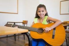 Allievo sveglio che gioca chitarra in aula Fotografie Stock Libere da Diritti