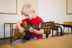 Allievo sveglio che gioca chitarra in aula Fotografia Stock Libera da Diritti