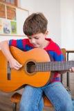 Allievo sveglio che gioca chitarra in aula Fotografie Stock