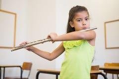 Allievo sveglio che gioca flauto in aula Fotografie Stock