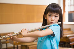 Allievo sveglio che gioca flauto in aula Fotografia Stock Libera da Diritti