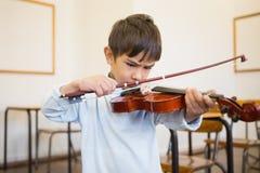 Allievo sveglio che gioca violino in aula Fotografia Stock Libera da Diritti